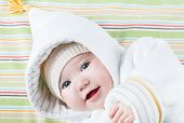 foto of blanket snow  - Cute Baby In A Funny Hat On A Colorful Blanket - JPG