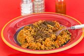 foto of okra  - Serving of Okra Gumbo over plate of Sausage Jambalaya on bright red background with Louisiana Hot Sauce and Cajun Seasoning - JPG
