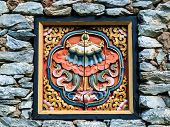 stock photo of rock carving  - Bhutan traditional wooden decoration in rock wall - JPG