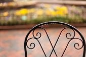 image of gatlinburg  - Rain drops on a chair back with flowers out of focus in the background - JPG