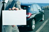 stock photo of courtesy  - closeup of a man in suit holding a blank signboard with a car in the background - JPG
