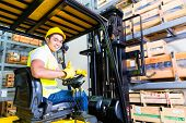 foto of lift truck  - Asian fork lift truck driver lifting pallet in storage warehouse - JPG