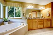 image of tub  - Bright bathroom with corner bath tub cabinet with granite top and large mirror - JPG