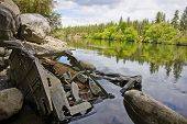 image of discard  - Horizontal photo of discarded television eroding in a river - JPG