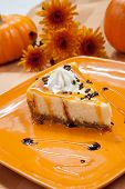 picture of cheesecake  - Sprinkle covered cheesecake with caramel and chocolate syrup with pumpkins and flowers in fall theme - JPG