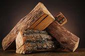 stock photo of floor heating  - Heap of firewood on floor on dark background - JPG