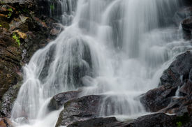 stock photo of gushing  - Water gushes over rocks at Amicacola Falls State Park - JPG