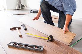 stock photo of laminate  - Man installing new laminated wooden floor - JPG