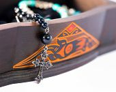 pic of rosary  - A rosary coming out of a carved box in wood - JPG