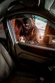 picture of scum  - Robber and the car thief in a mask opens the door of the car and hijacks the car - JPG