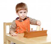 foto of kindergarten  - Little boy plays to develop the game sitting at the table - JPG
