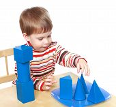 pic of montessori school  - Little boy plays cubes and cones sitting at the table - JPG