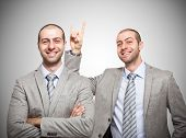 stock photo of prank  - Funny businessman making the horns sign to himself - JPG