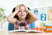 stock photo of unbelievable  - Astonished kid girl reading a book in nursery at home - JPG