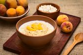 picture of peach  - Bowl of oatmeal porridge served with peach slices photographed with natural light  - JPG