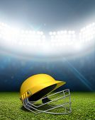 stock photo of cricket  - A cricket stadium with a yellow cricket helmet on an unmarked green grass pitch at night under illuminated floodlights - JPG
