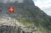 stock photo of flutter  - Swiss flag fluttering on wind high in mountains nearby Grindelwald in Alps in Switzerland - JPG