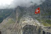 foto of flutter  - Swiss flag fluttering on wind high in mountains nearby Grindelwald in Alps in Switzerland - JPG