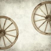 stock photo of wagon wheel  - textured old paper background with old wagon wheel - JPG