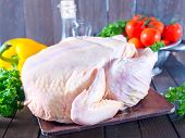 stock photo of gobbler  - raw chicken and fresh vegetables on a table - JPG