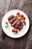 stock photo of ribeye steak  - Sliced medium rare grilled Beef steak Ribeye with grilled onions and cherry tomatoes on plate on wooden background - JPG