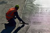 picture of concrete pouring  - A builder floating off new concrete for a large building - JPG