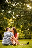 stock photo of barefoot  - Young smiling couple sitting and kissing on grass  - JPG