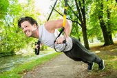 picture of suspension  - man exercising with suspension trainer sling in City Park under summer trees for sport fitness - JPG
