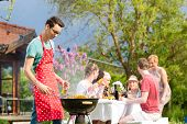 stock photo of bbq party  - Family and friends having bbq at garden party - JPG