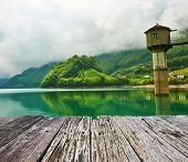 stock photo of emerald  - Beautiful emerald mountain lake in Switzerland under low clouds - JPG