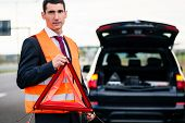 picture of breakdown  - Man with car breakdown erecting warning triangle on road - JPG