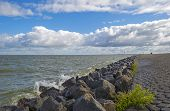 stock photo of dike  - Deteriorating weather over a dike along a sea in spring