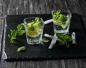 foto of mojito  - Two glasses of mojito cocktail on a black slate board - JPG