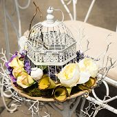 foto of caged  - decorative flowers in retro vintage bird cage - JPG