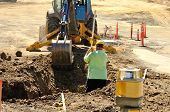 stock photo of street-rod  - Construction excavation contractor uses a level rod and laser to dig a trench for a concrete fondation wall - JPG