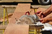 picture of worm  - Building contractor worker using hand held worm drive circular saw to cut boards on a new home construciton project - JPG