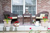 image of spring break  - Wicker furniture on the patio with a samovar and tea cups ready for a relaxing tea break in the spring sunshine with pretty flowering potted plants - JPG