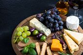 stock photo of cheese platter  - Cheese board with fresh grapesherbs and olives red wine - JPG