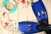 foto of flipper  - Sea composition with flippers and shells on wooden table close up - JPG