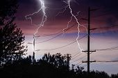 stock photo of lightning  - Silhouette of Power Lines being struck by lightning - JPG