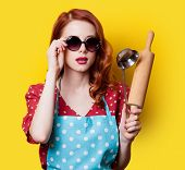 picture of plunger  - Surprised redhead girl in red polka dot dress with plunger on yellow background - JPG