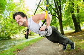 foto of suspension  - man exercising with suspension trainer sling in City Park under summer trees for sport fitness - JPG