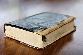 image of leather-bound  - Close up on a black leather bound tattered and torn old vintage book the Holy Bible sitting on Wooden Table - JPG