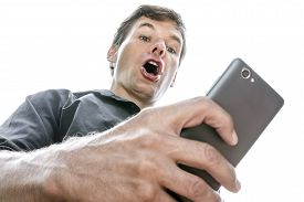 stock photo of shock awe  - Low angle closeup Caucasian man looking down at his cell phone shows expression of shock as he opens his mouth in disbelief on white background - JPG