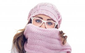 picture of freezing  - Freezing young woman hiding behind her scarf or winter clothing isolated on white - JPG
