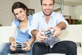 Young man and young woman playing video game poster
