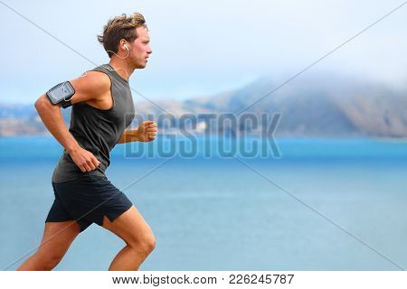poster of Running app on smartphone. Male runner listening to music jogging with armband for smart phone. Fit