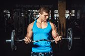 Muscular Man Lifting Weights On Biceps And Looks At The Biceps Over Dark Background poster
