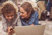 Happy Kid And Beaming Mother Watching At Notebook Computer While Locating On Carpet. Appliance Conce poster