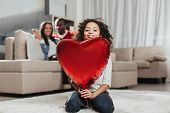 Family Harmony. Calm Girl Looking Happy While Sitting In Apartment With Toy Heart In Hands. Parents  poster